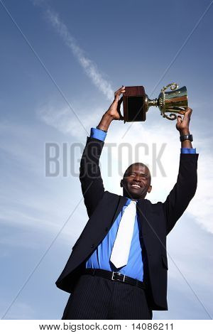 Businessman holding up trophy