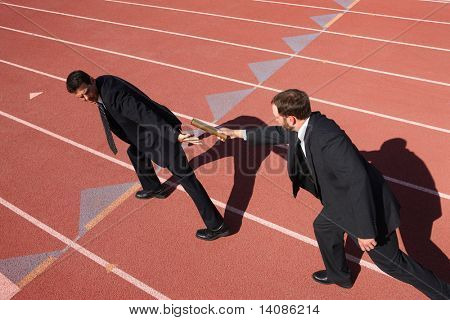 Businessmen passing the baton in a track relay