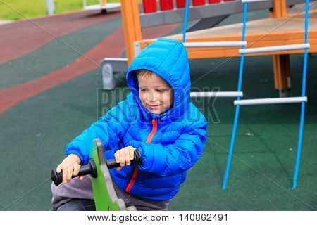 child having fun on the playground riding on the spring horse, daycare