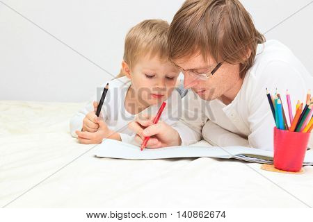 father and son drawing or writing, education and daycare