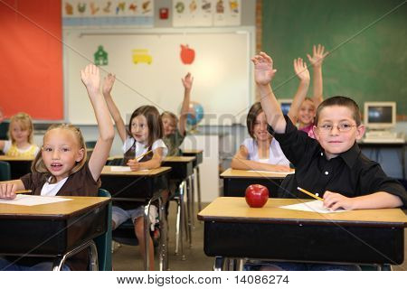 Elementary school students raising hands