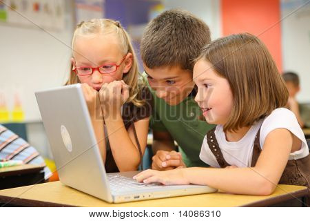 Elementary school students looking at computer