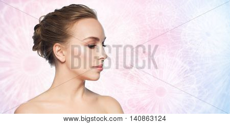 health, people, plastic surgery and beauty concept - beautiful young woman face over rose quartz and serenity patterned background