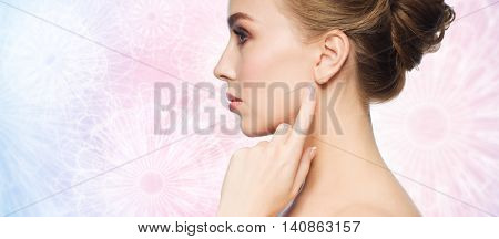 health, people and beauty concept - beautiful young woman pointing finger to her ear over rose quartz and serenity patterned background