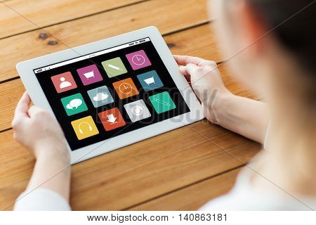 technology, people and multimedia concept - close up of woman with menu icons tablet pc computer screen on wooden table