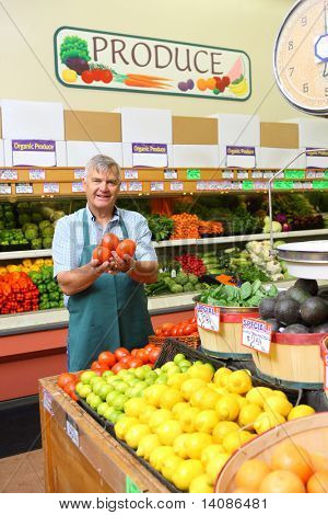 Man holding tomatoes in grocery store