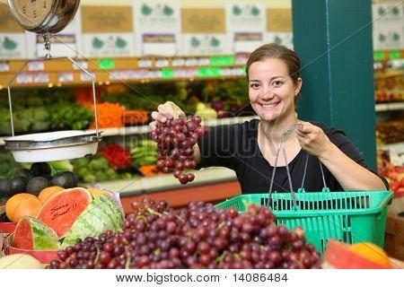 Mulher no supermercado pegando uvas
