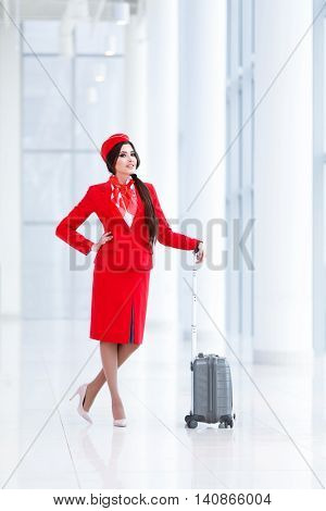 Smiling stewardess with a suitcase