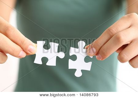 Hands holding two matching puzzle pieces