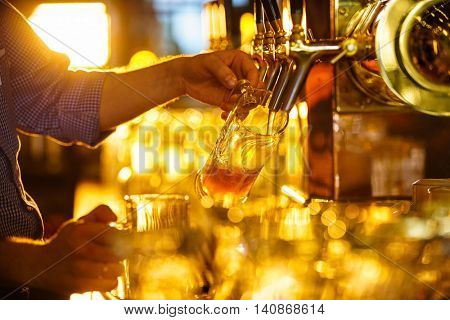 Male hands poured beer from the tap