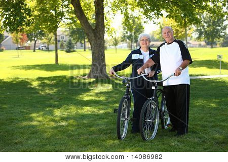 Senior couple with bikes at park