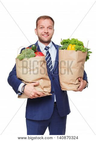 Smiling young businessman hold shopping bags full of groceries isolated at white background. Healthy food shopping. Paper package with vegetables and fruits, happy man buyer show thumb up