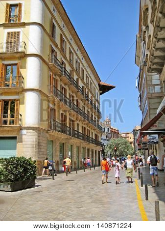 Palma de Majorca Spain - June 25 2008: Street Placa de Santa Eulalia with stores and aparment buildings and walking people / tourists