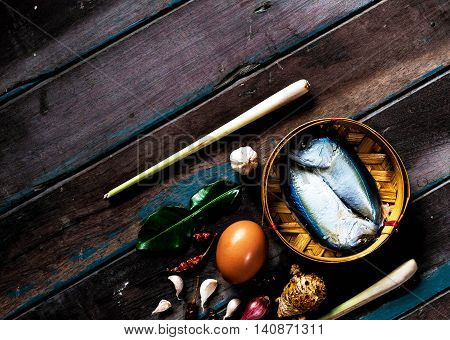 Fish and eggs before cooking on a wooden