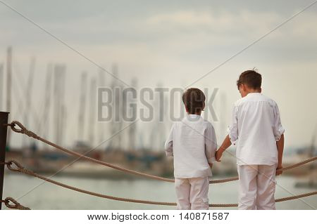 Two Similar Brother Standing On Waterfront,