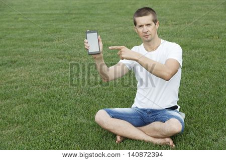 VOLGOGRAD RUSSIA - July 23 2016: The guy in a t-shirt and jeans shorts points a finger at phone sitting on a green grass