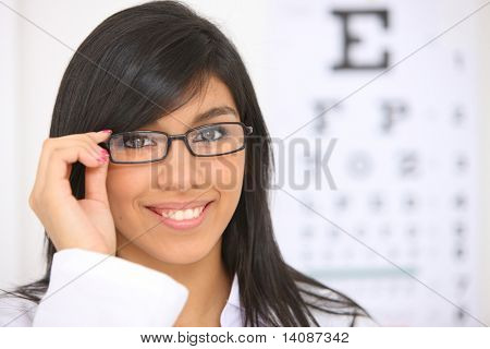 Young woman with glasses, eye chart in background