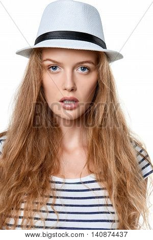 Closeup portrait of young woman in white straw hat staring at camera, over white background