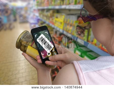 Woman is shopping in supermarket and scanning barcode with smartphone in grocery store to get online info about product.