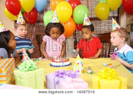 Young girl blowing out candles at birthday party