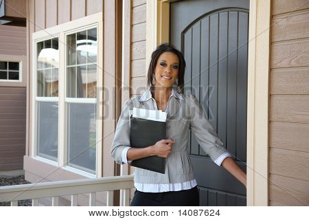 Young female Realtor opening front door of home