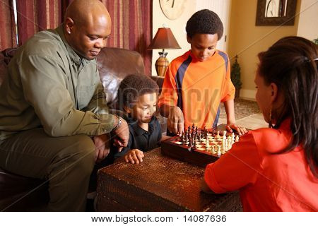 Family in living room playing chess together