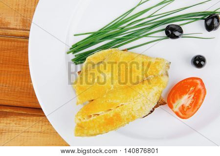 savory: fish fillet served on plate over wood with tomatoes,olives and bread