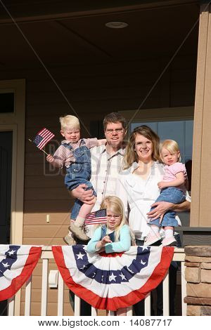 Patriotic family on front porch with children waving flags