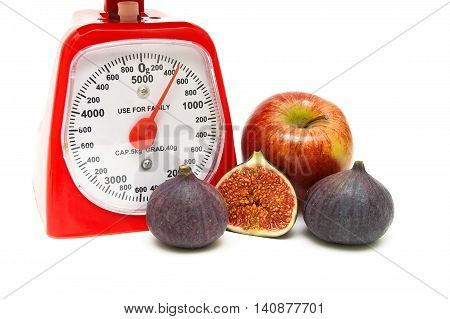 kitchen scale fig and apple on a white background. horizontal photo.