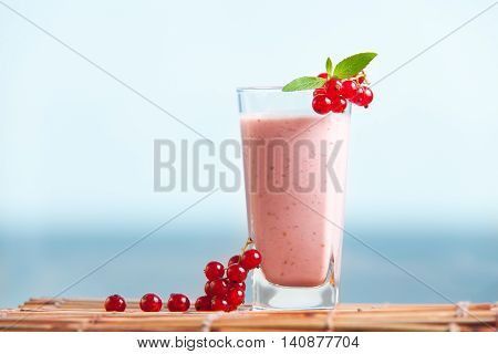 Red currant milkshake with mint leaves and sea on the background. Healthy summer drink with milk and icecream. Cold fresh smoothie.