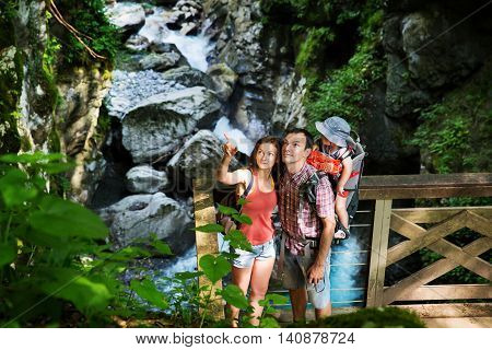 Active family hiking with 15 years child in carrier on the background of a mountain river. Slovenia Tolmin Waterfalls of the Kozjak Tolmin Gorges.