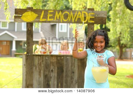 Girl holding lemonade in front of lemonade stand
