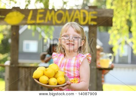 Girl holding bowl of lemons