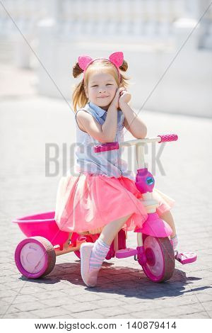 Little girl with blond hair, hair in two tails, color is pink hoop hair with pink ears, wearing a light blue sleeveless shirt and pink skirt, riding a pink bicycle in the children in the city of the great outdoors in the summer
