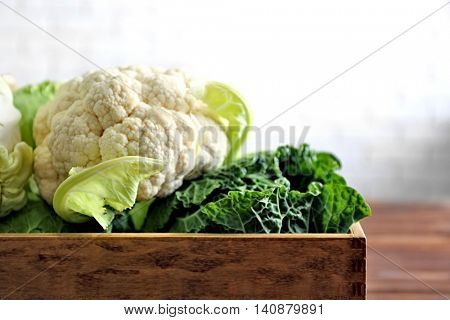 Fresh cabbage in wooden crate on brick wall background
