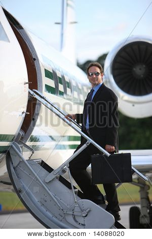 Businessman standing on stairs to private jet