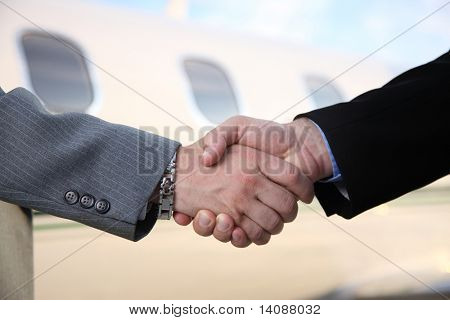 Businessmen shake hands in front of jet