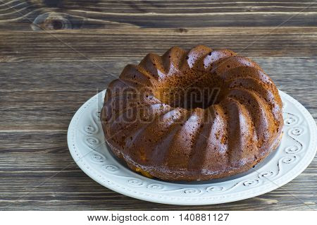 Bundt cake on a white plate  on a wooden background.