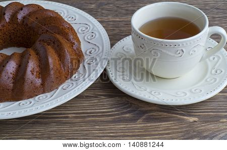 Bundt cake with tea  on a wooden background.
