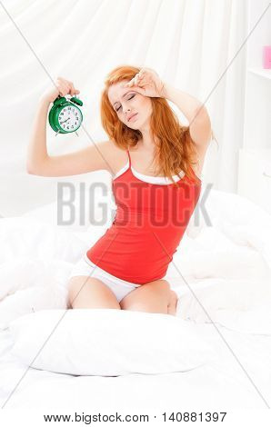 Beautiful girl woke up and sitting on a bed in the early morning. Beautiful young woman in underwear holding alarm-clock in the bedroom.