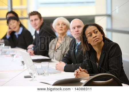 Businesspeople watch presentation in board room