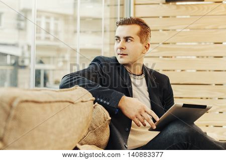 Young man in caffe holding digital tablet and looking out the window