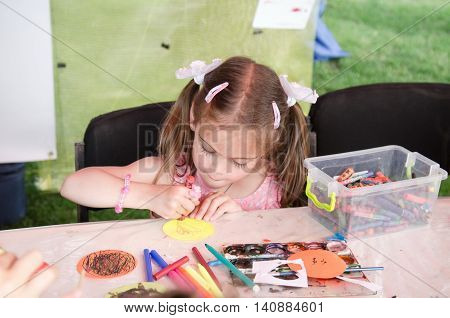 KHARKIV UKRAINE - JUNE 18 2016: Day of music held in Kharkiv Ukraine. Unidentified girl is drawing elementary pictures in the playground for children.