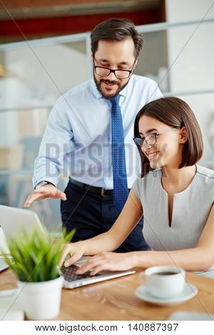 Businessman communicating with businesswoman while she typing on laptop