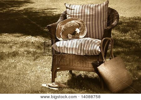 Straw hat, old wicker chair waiting for someone to relax  on a hot summer's day/sepia tone