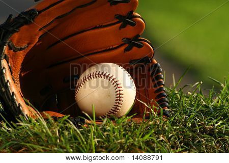 Baseball and glove on the grass after the big game