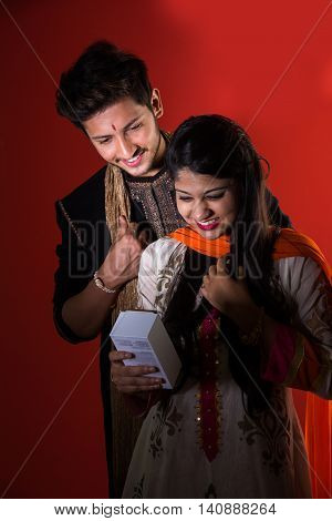 Indian sister flaunting or showing her rakshabandhan gift, a smartphone, brother standing behind