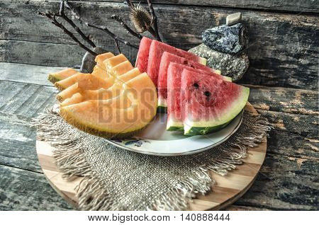Old wooden board with porcelain a plate and slices of melon and watermelon
