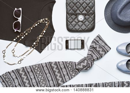 Street style. Urban girl handbag smartphone black top glamor shoes trendy necklace blue hat and sunglasses. Urban Fashion summer clothes accessories set.Overhead outfit top view gray background