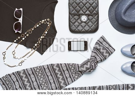 Street style. Urban girl, handbag, smartphone, black top, glamor shoes, trendy necklace, blue hat and sunglasses. Urban Fashion summer clothes accessories set.Overhead outfit, top view gray background